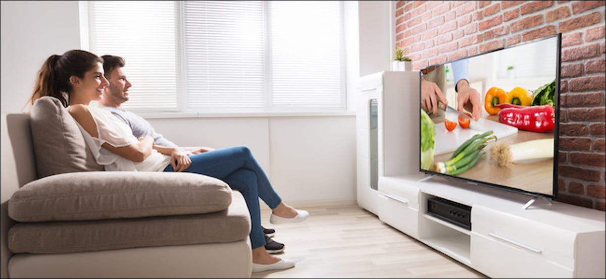 A couple watch a food show on TV