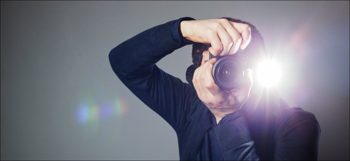 A man takes a picture on a camera with a built-in flash.