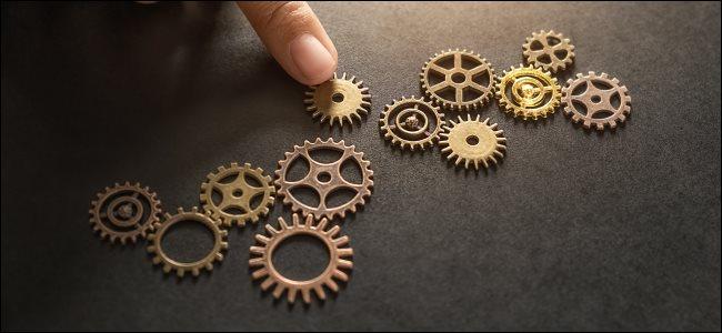 A hand placing a clockwork gear into position.