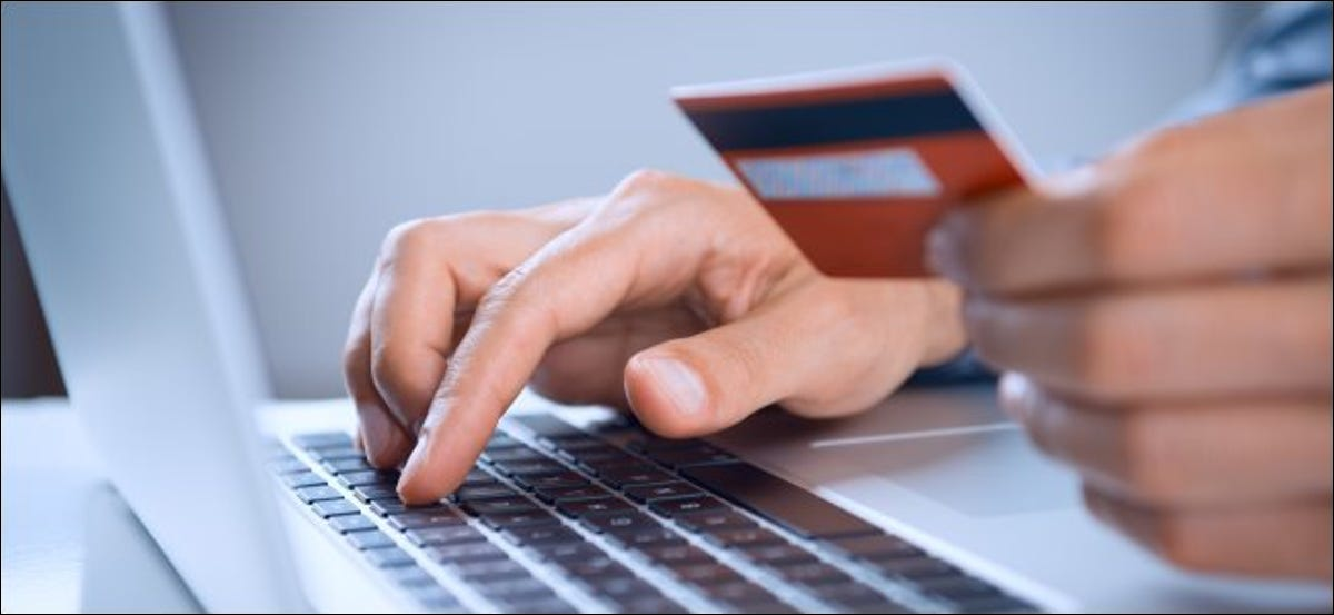 A person holding a credit or debit card while typing on a laptop.
