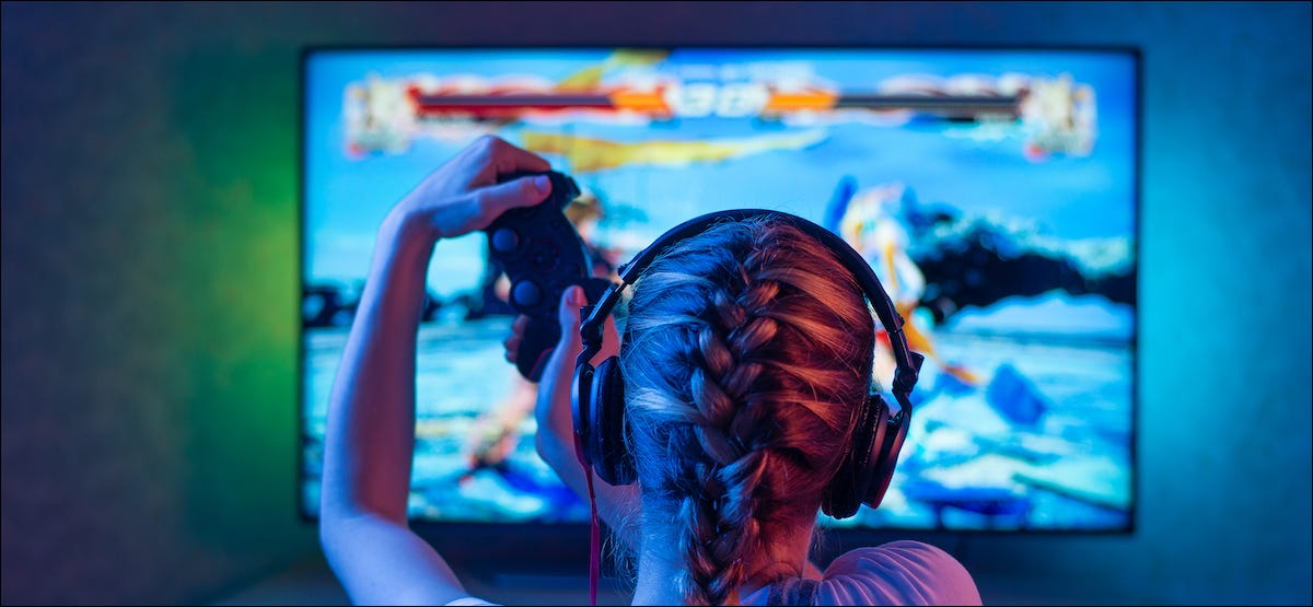Person playing video games on a TV with back lighting