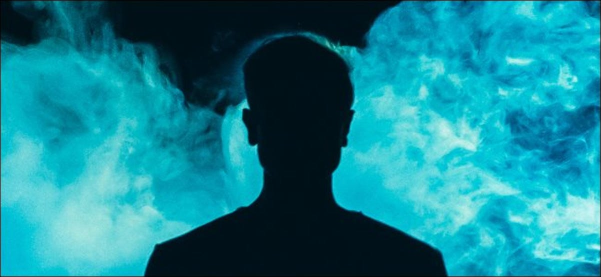 A silhouette of an individual in front of blue smoke over a dark background.