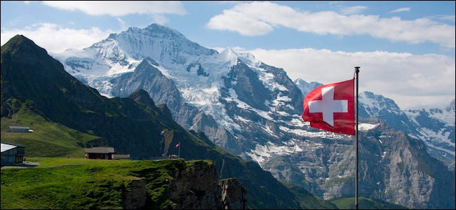 Swiss flag flown in front of a mountain