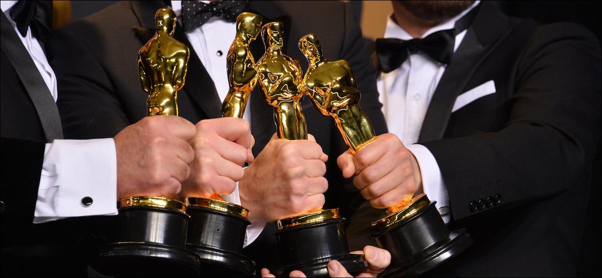 Three men holding Oscar awards