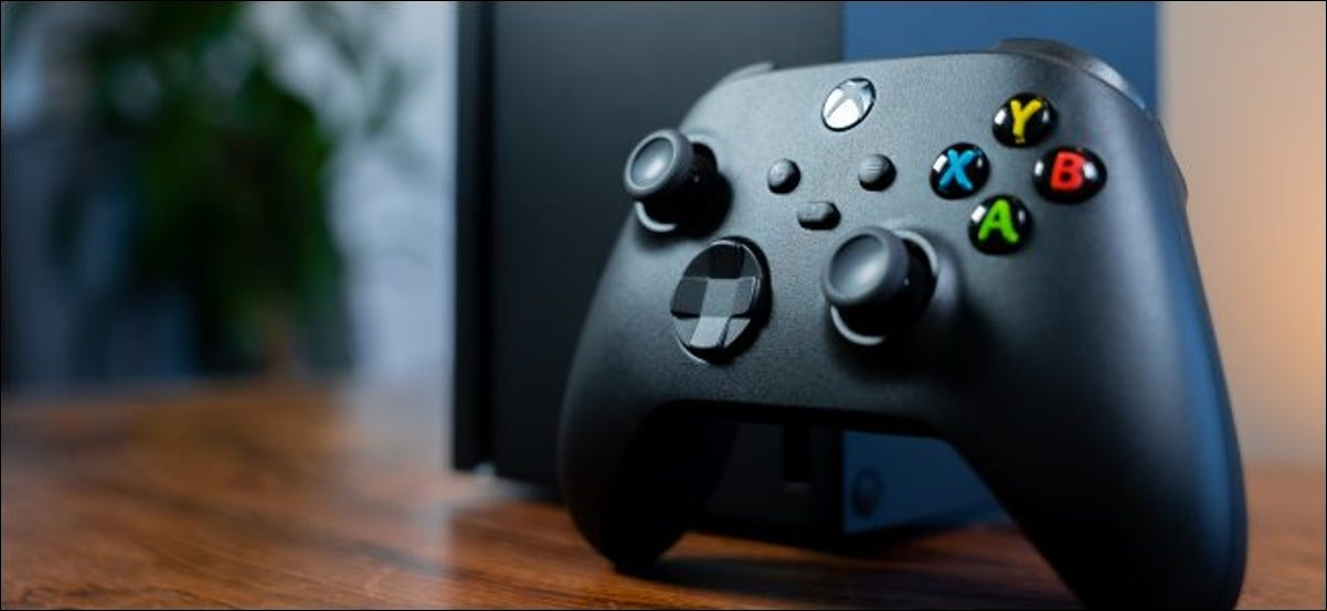 An Xbox controller with an Xbox Series X in the background