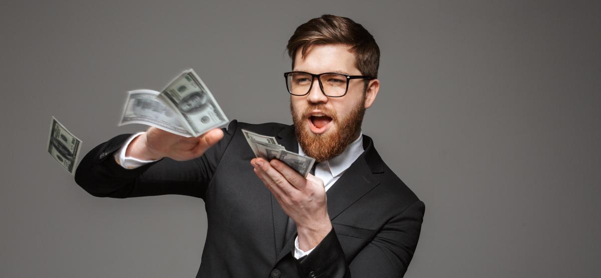 A businessman throwing money around.