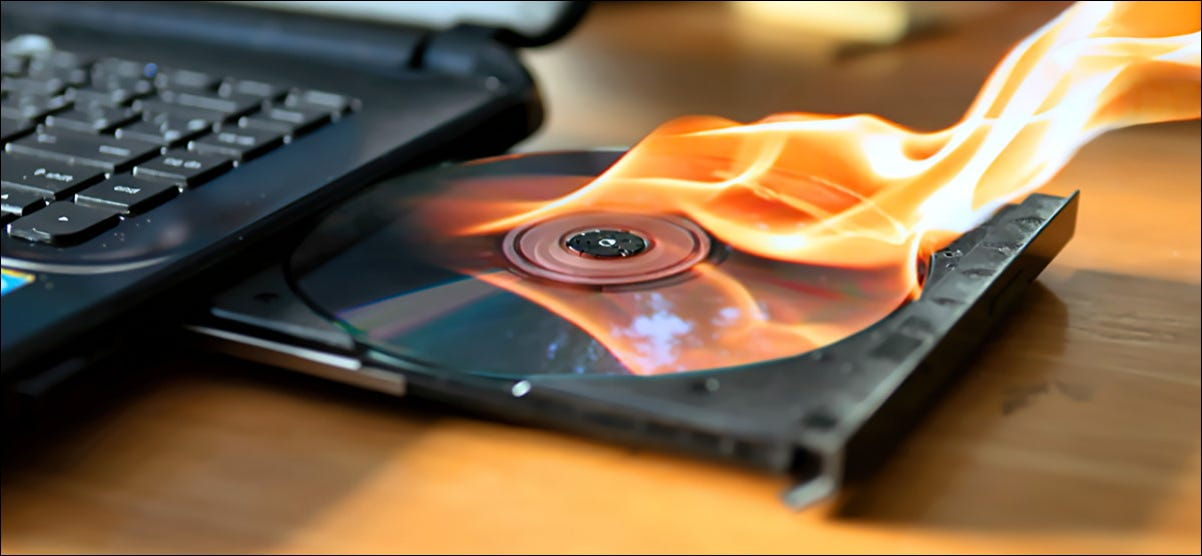 Burning a CD in a laptop drive.