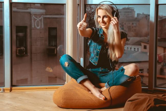 Женщина слушает в наушниках и показывает палец вверх.