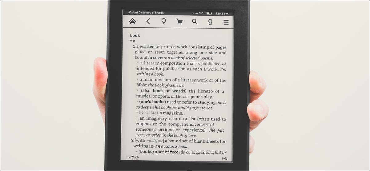 A hand holding a Kindle Paperwhite eBook reader.