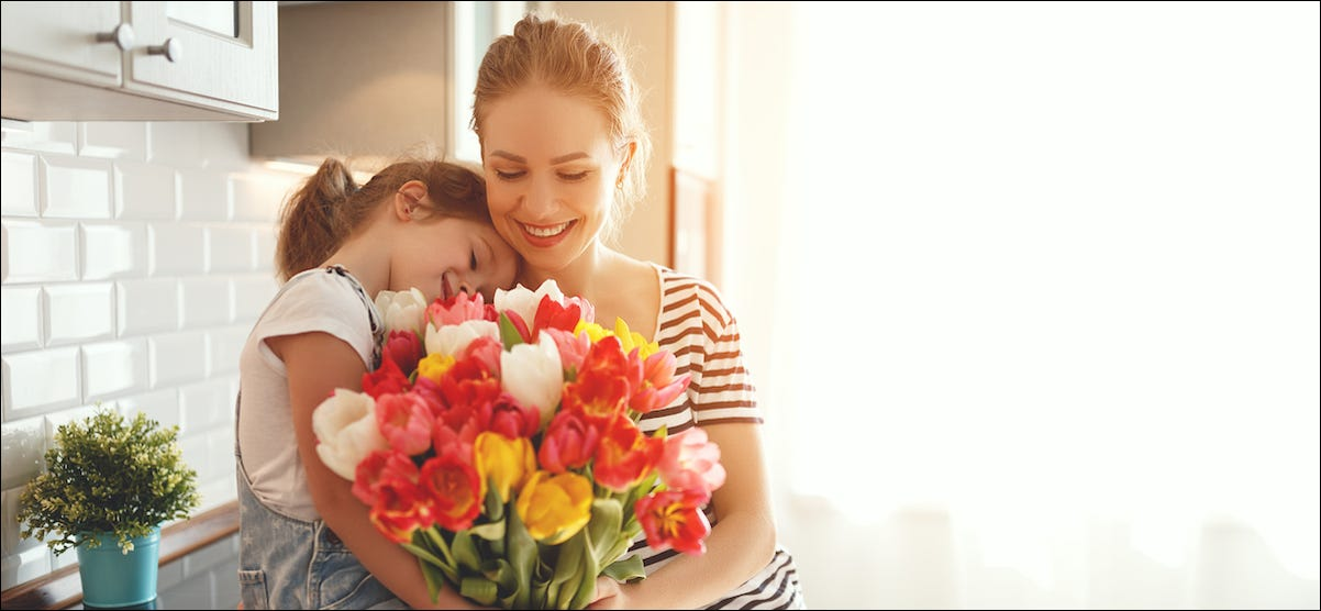 Mother and daughter holding flowers and celebrating Mother's Day