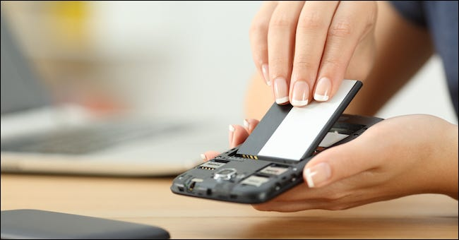 person removing the battery from a smartphone
