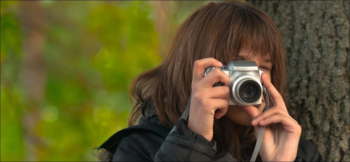 A person taking pictures with a point and shoot camera.