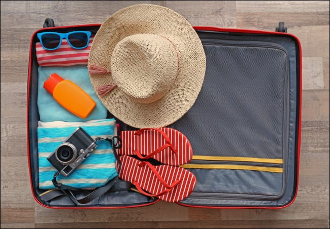 An open suitcase packed for a vacation.