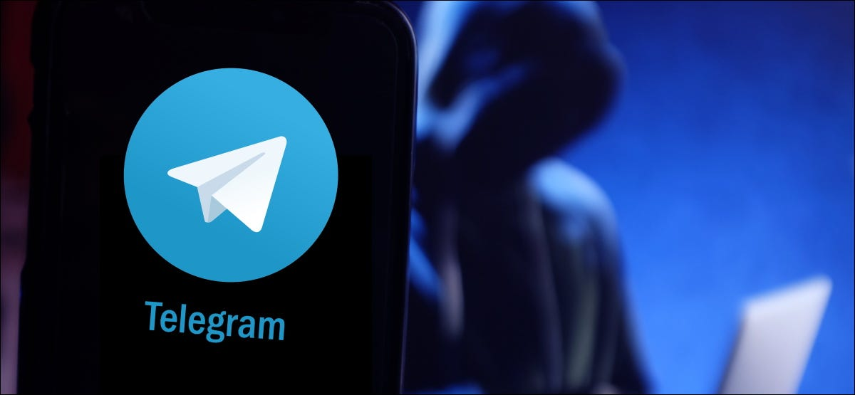A shadowy figure on a laptop behind a smartphone with a Telegram logo.