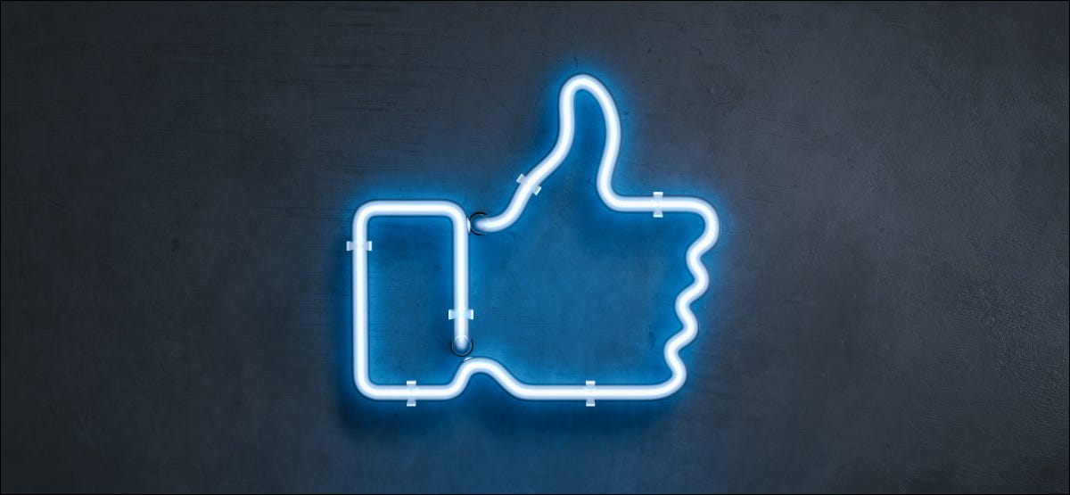 A blue neon sign of a thumbs up on a wall.