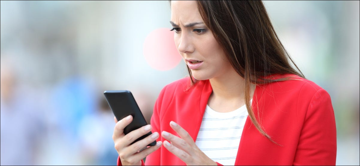 A worried woman looking at her smartphone.