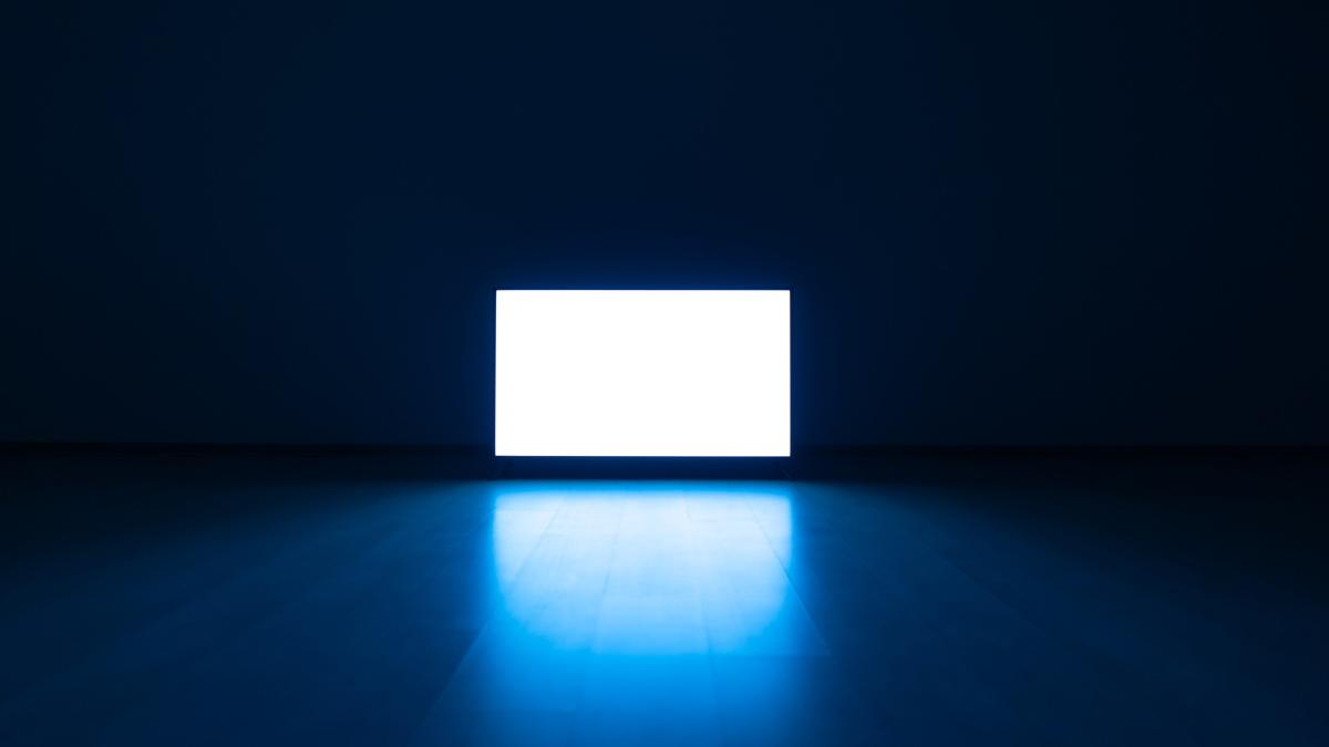 A bright television in a dark room.