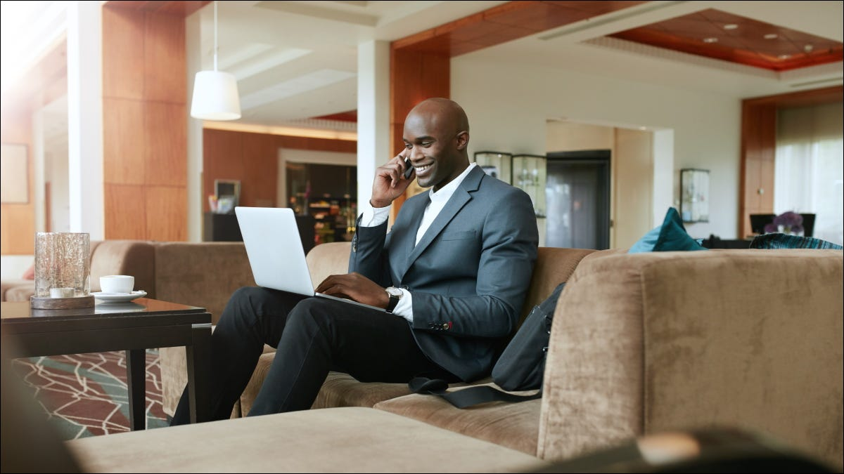 A businessman sitting in the lobby of a hotel and working on a laptop.