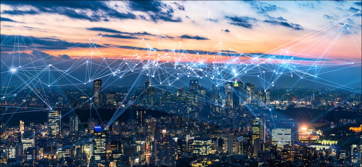 A cityscape with digital connections drawn above it.