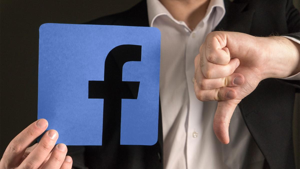 A man giving a thumbs down to a Facebook logo.