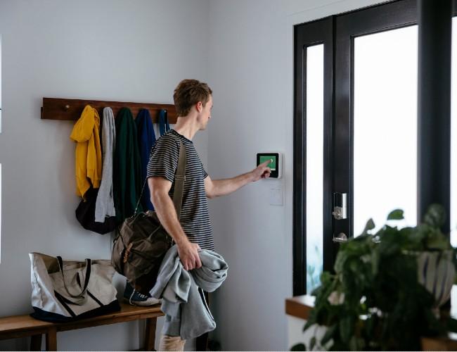Человек с помощью сенсорной панели у входной двери