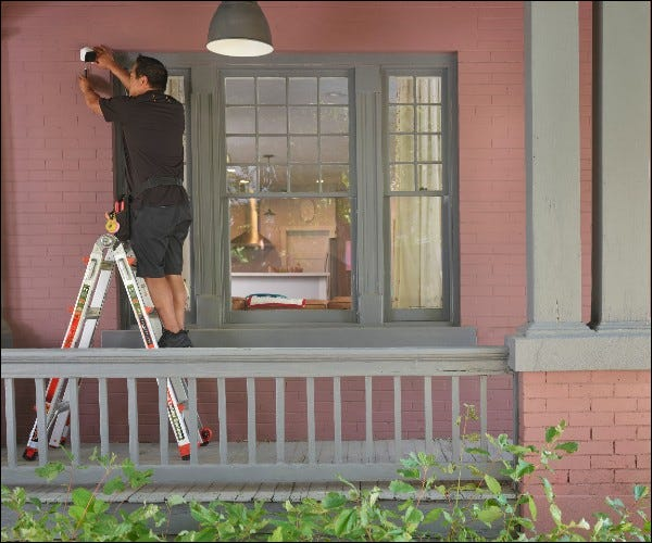 Человек, устанавливающий камеру вне дома