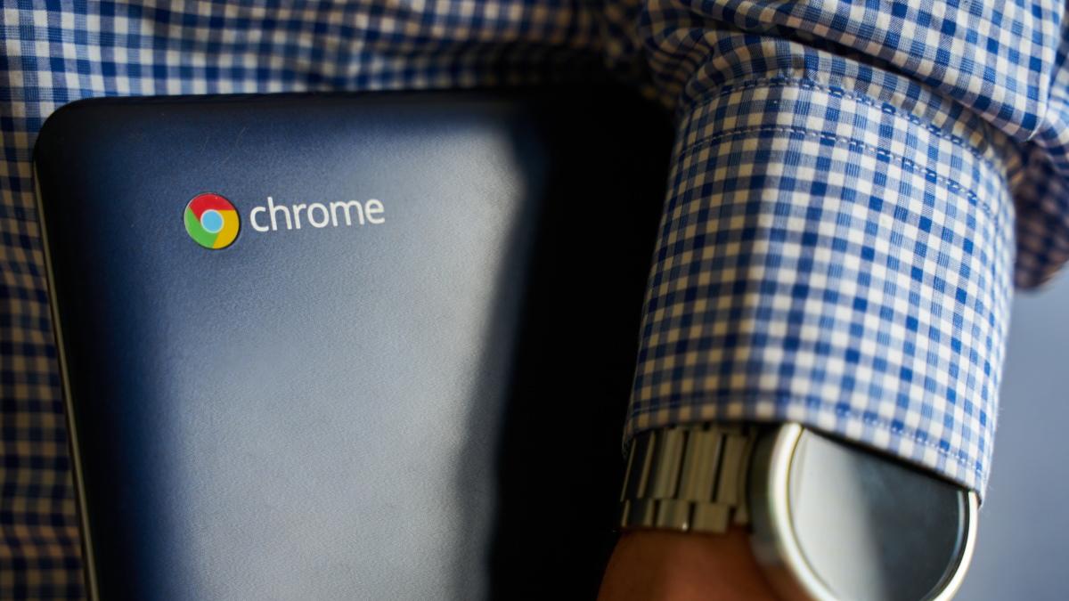Человек, держащий под мышкой Asus Chromebook.