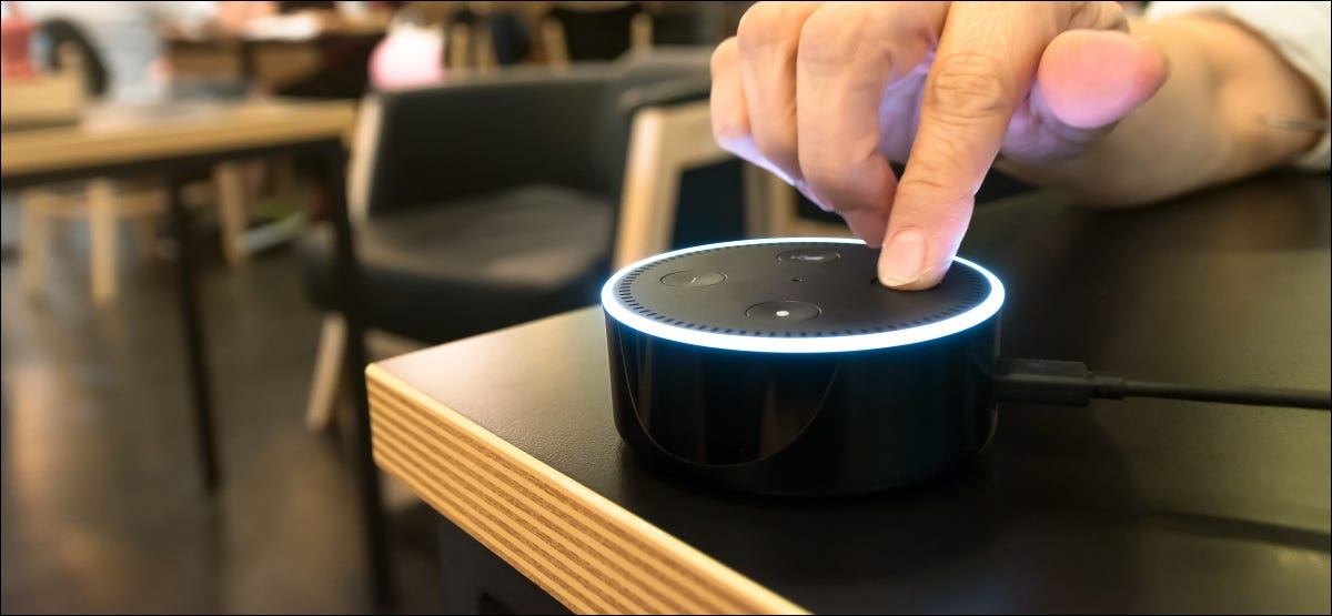 A finger pressing a button on an Amazon Echo Dot in a coffee shop.
