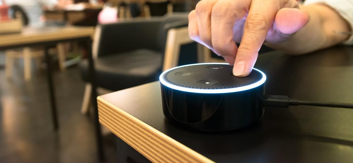 Палец, нажимающий кнопку на Amazon Echo Dot в кафе.