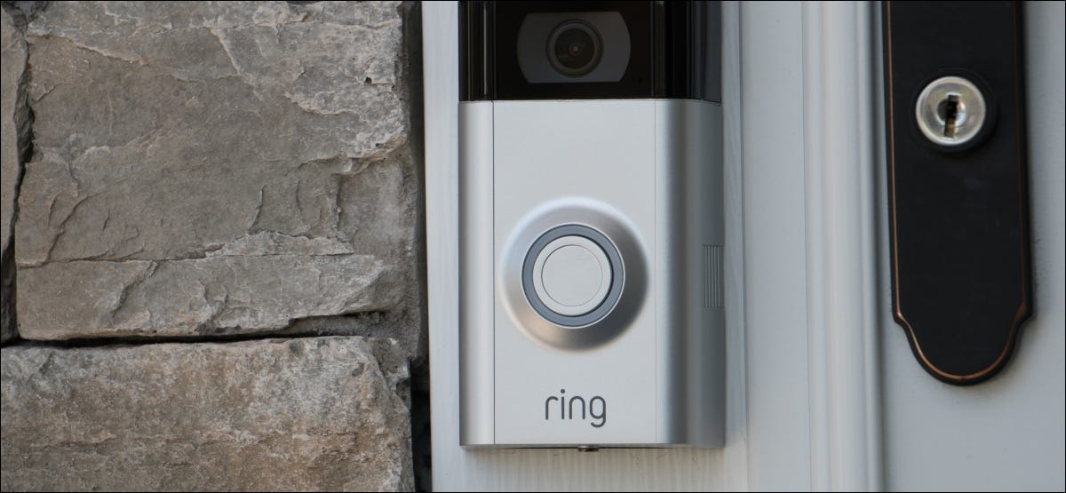 A Ring video doorbell mounted on a door frame.