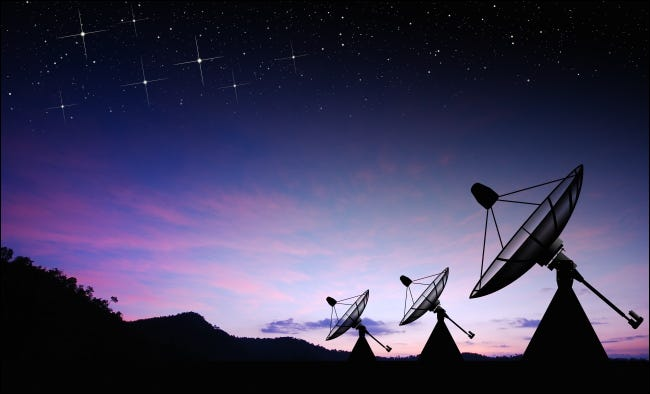 Satellite dishes against a sunset.