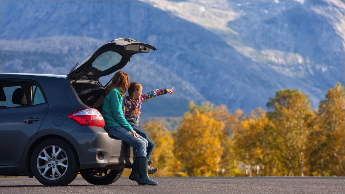 Tourists looking at a mountain from the back of their car.