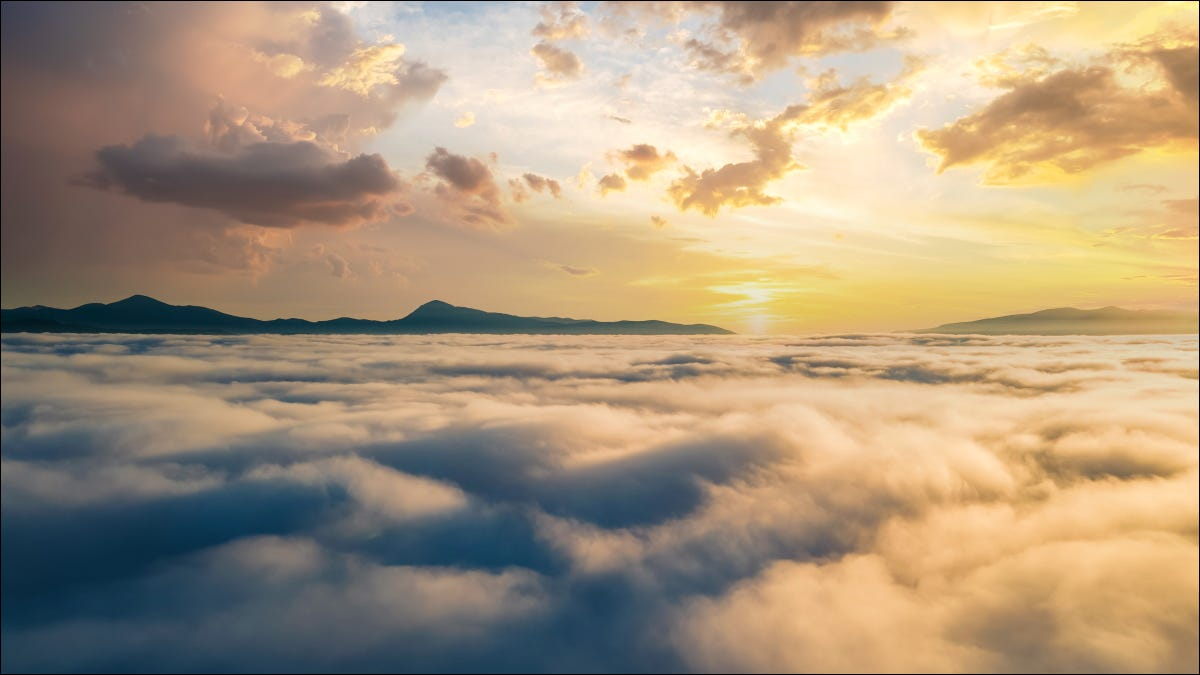 An aerial view of a sunset over dense clouds with mountains on the horizon.