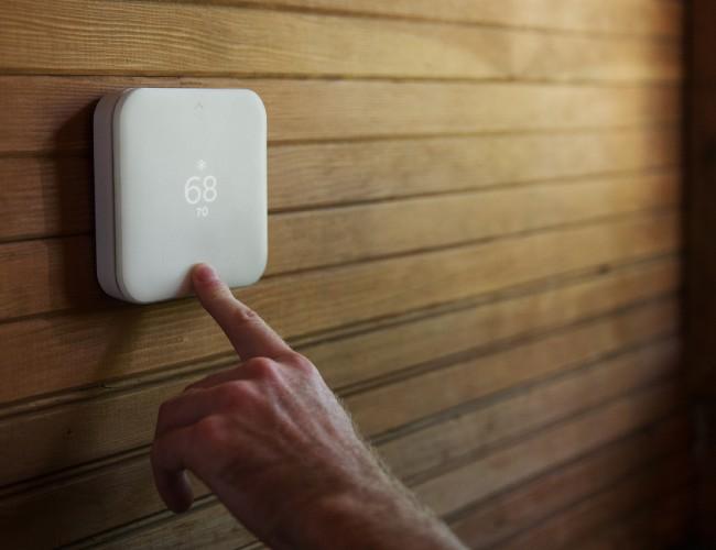 Квадратный белый термостат на деревянной стене