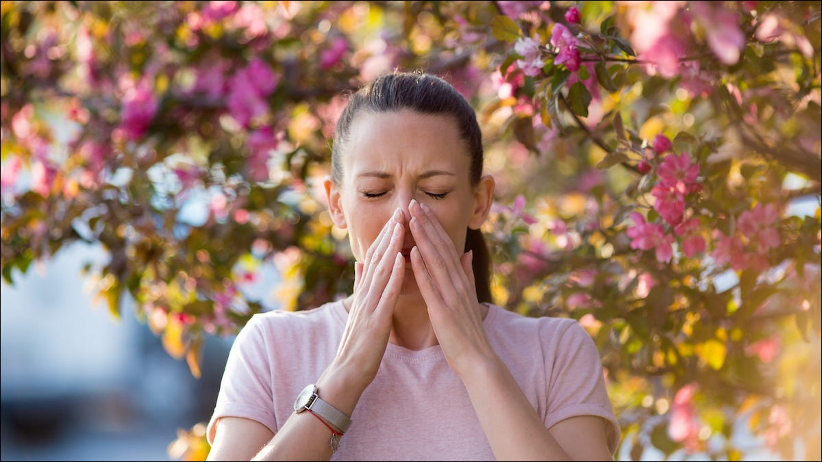 Woman standing under a tree sneezing from pollen allergies