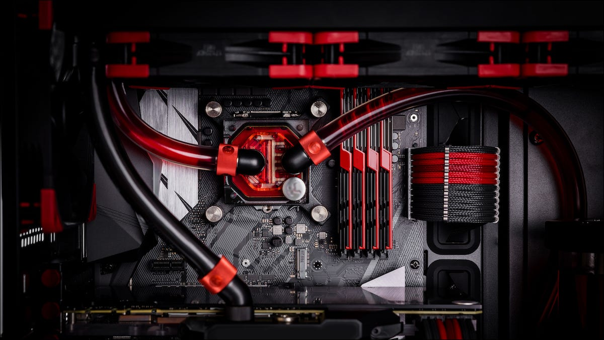 The inside of a gaming PC showing a motherboard with watercooling.