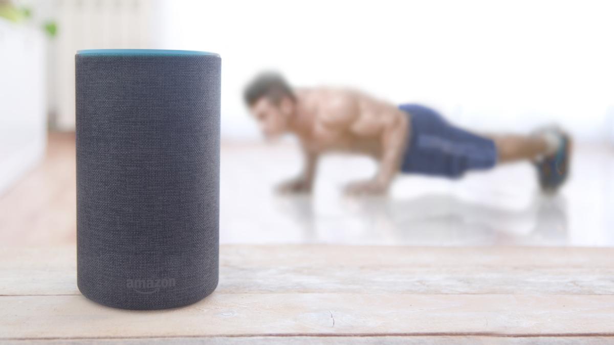 A man doing pushups behind an Amazon Echo Plus speaker.