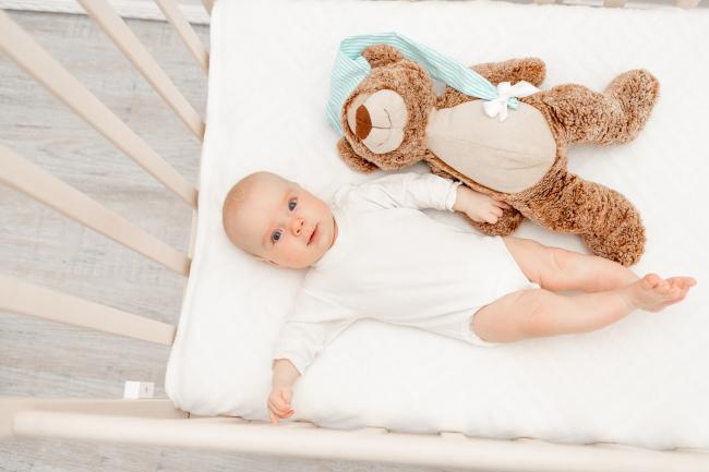 Ребенок в кроватке с плюшевым мишкой