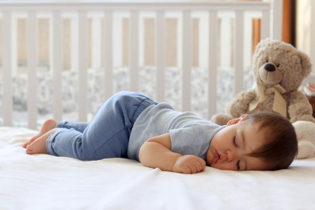 Ребенок спит в кроватке с плюшевым мишкой