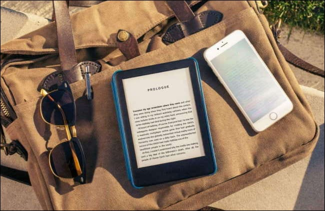 kindle in case on canvas bag with phone and sunglasses