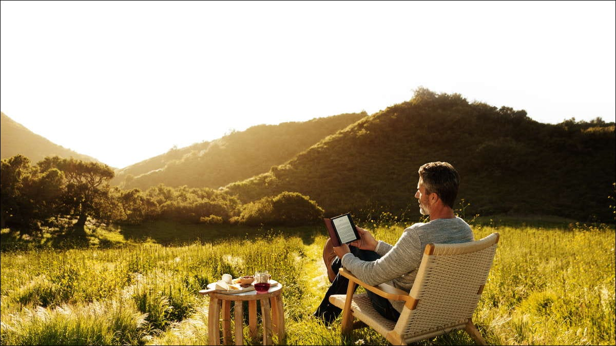 man reading kindle outside in hilly landscape