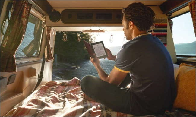 man reading kindle in back seat of van