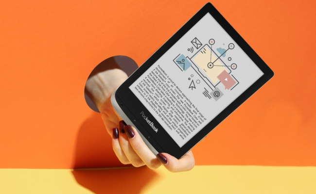 pocketbook color reader on orange background held by hand