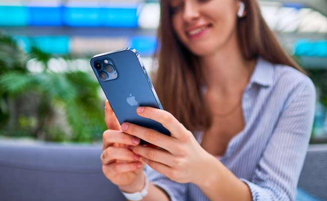 woman using blue iphone 10 pro max near greenary