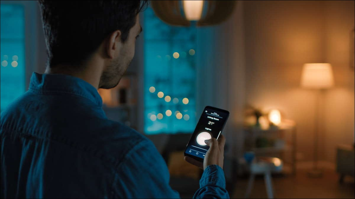 Person controlling their smart light bulbs using a smartphone