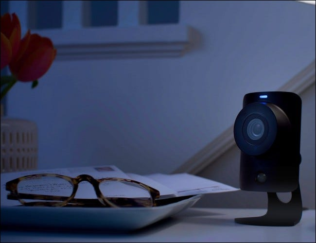 Camera next to glasses on table at night