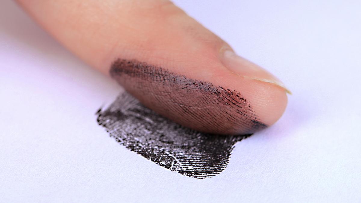 Снятие отпечатка пальца на белой бумаге.