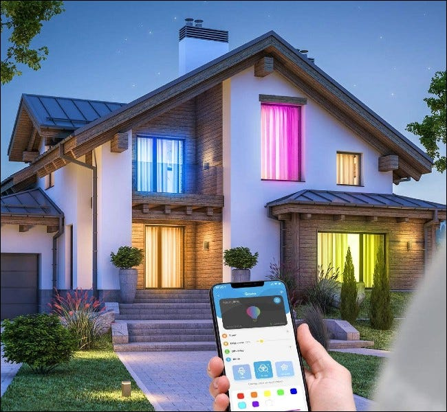 Person using app outside home with colored lights in the windows