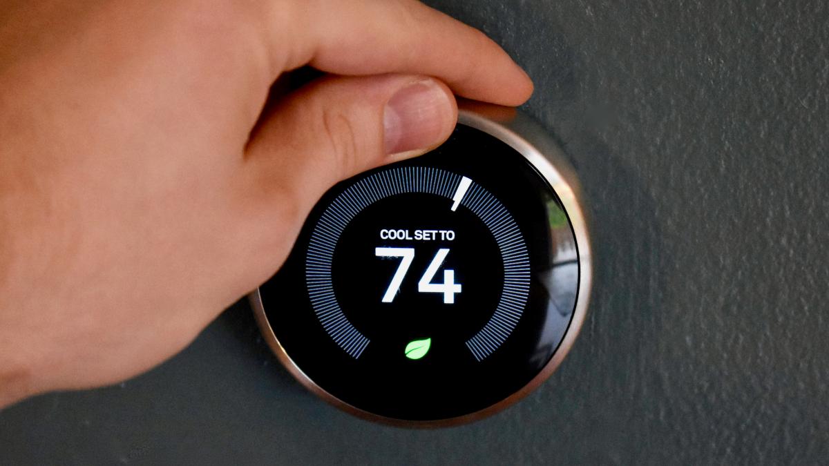 Hand adjusting a smart thermostat