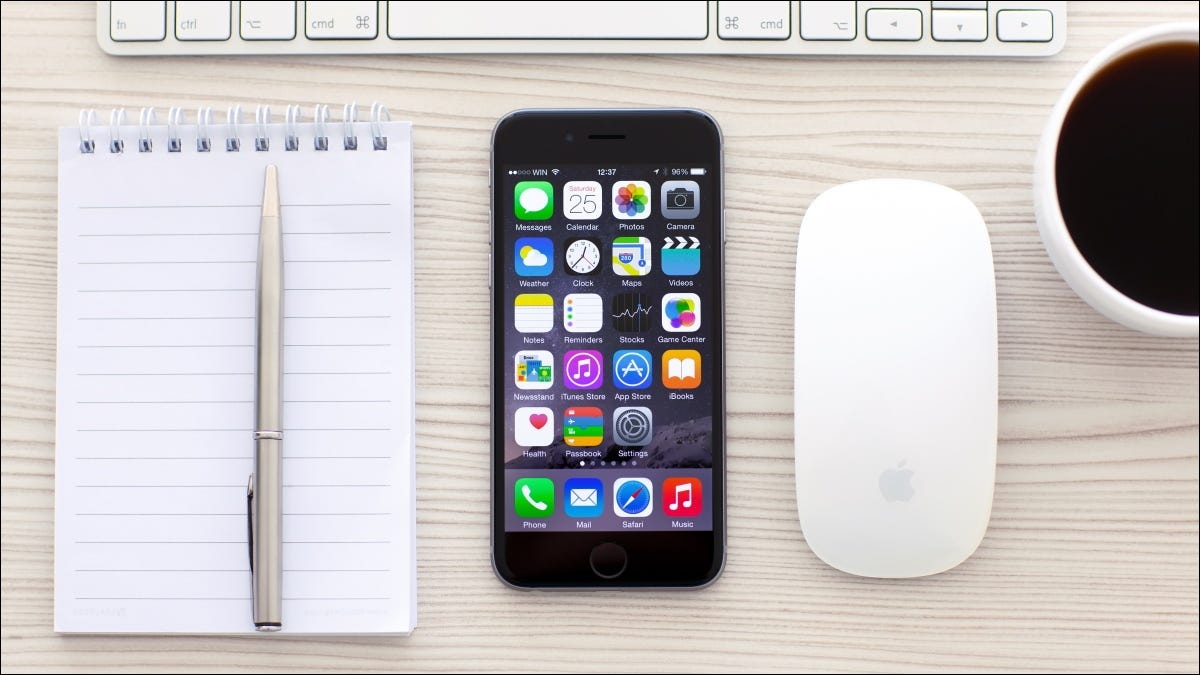 An iPhone sitting next to a wireless mouse and keyboard.